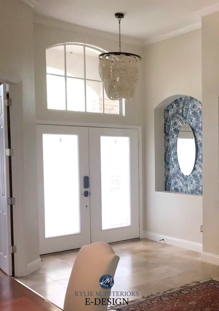 entryway painted with neutral ground double glass front doors with white surround and tile floor with beaded chandelier above