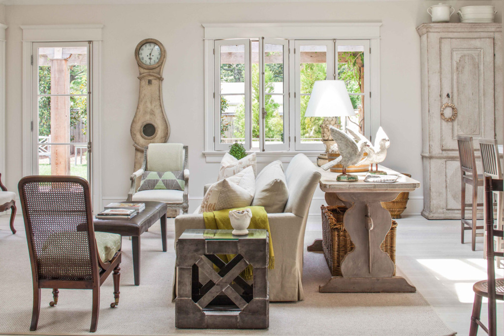 gustavian style family room with mora clock next to windows and slipcovered sofa with large table behind it