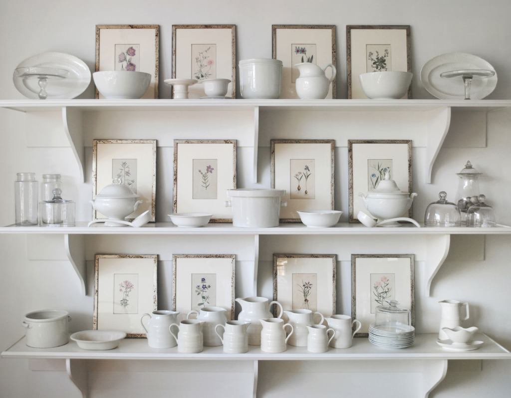 three white shelves holding a white ironstone collection with framed antique botanicals in leaning against the wall