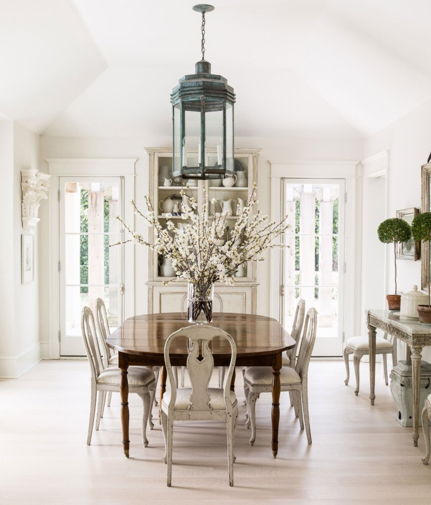 neutral dining room with vaulted ceiling and lantern chandelier over formal table with white gustavian dining chairs