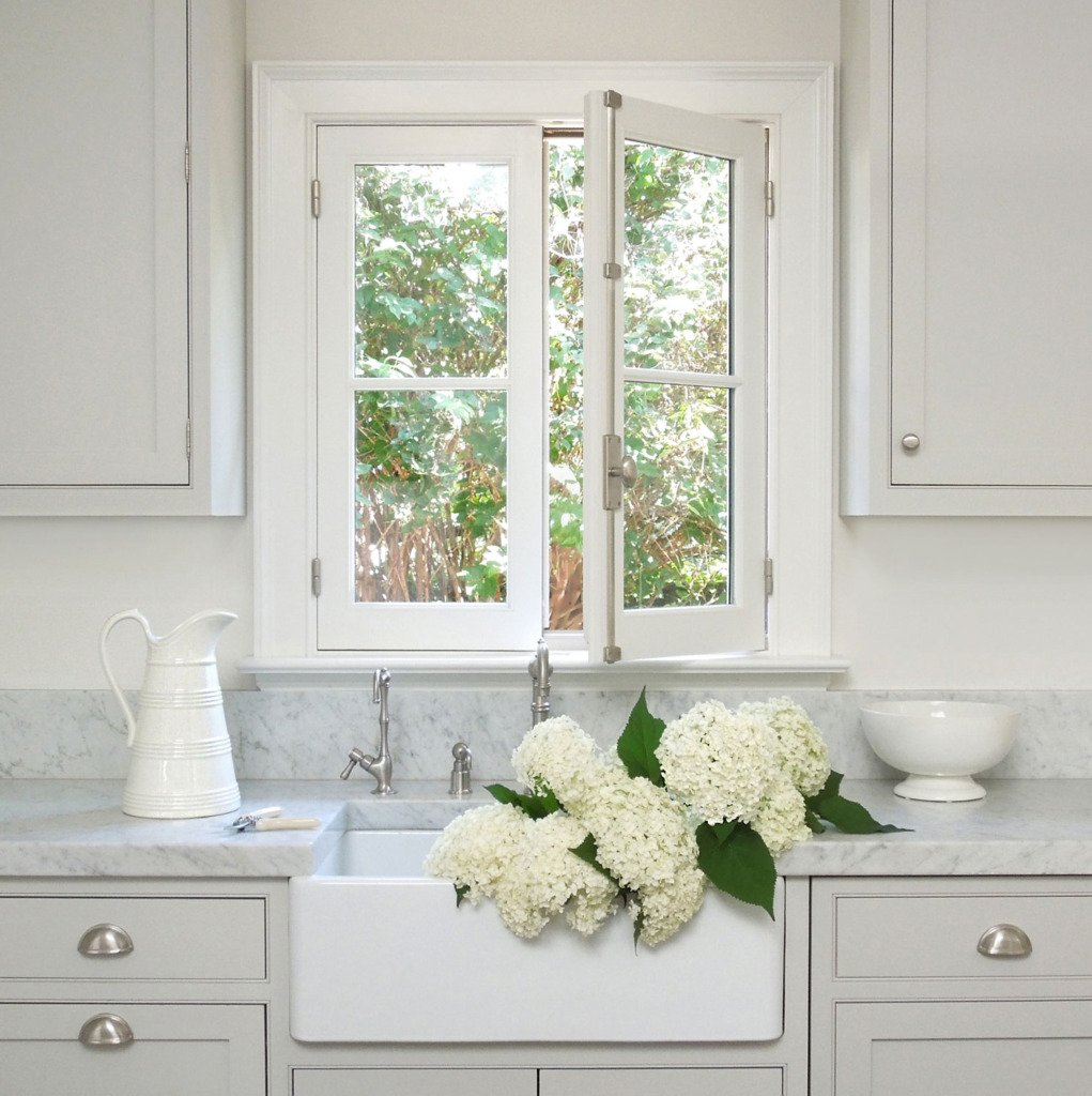 gray inset kitchen cabinets with carrera marble countertop and white farmhouse sink filled with white hydrangeas