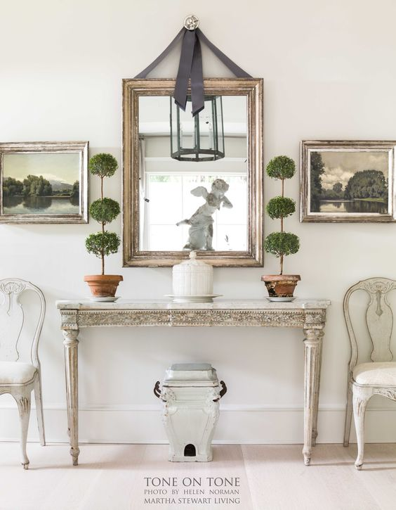 gustavian console table with gold mirror above hanging from gray ribbon and two triple ball myrtle topiaries on either side