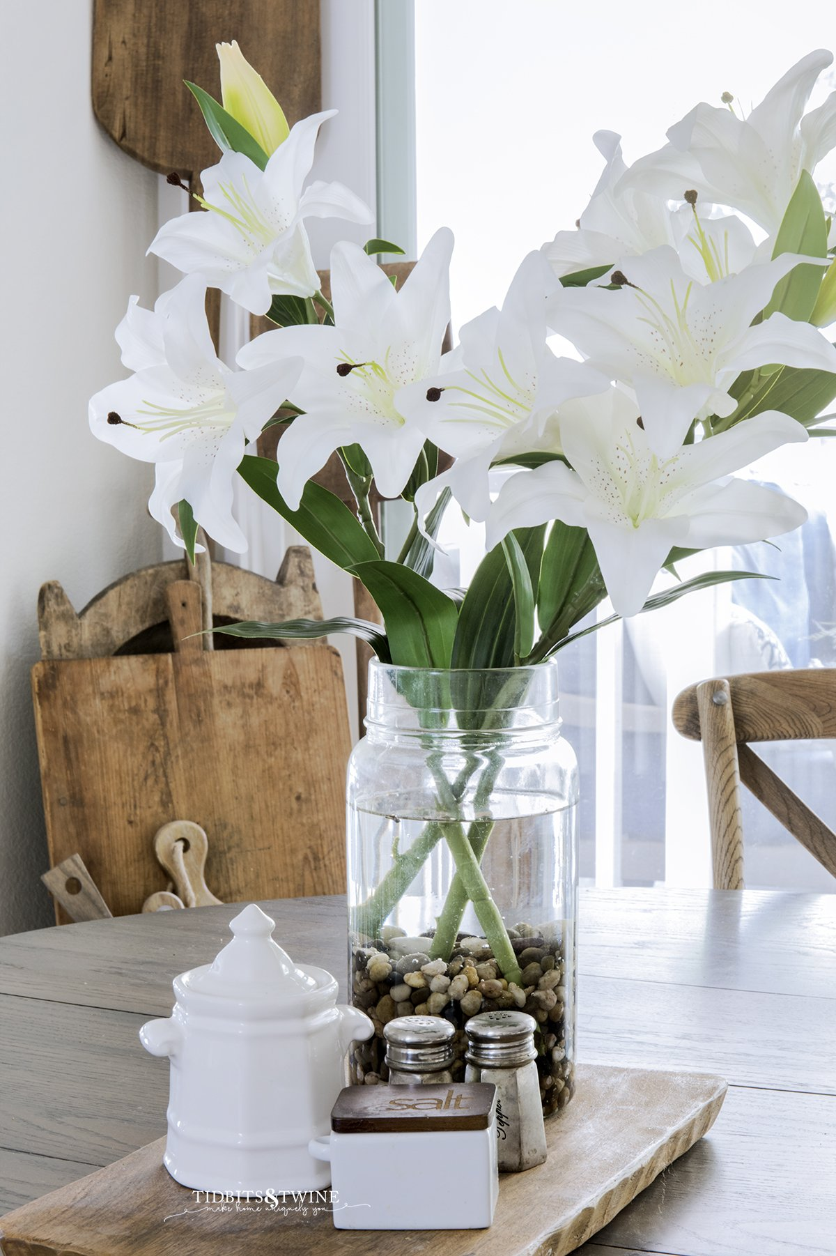 artificial white lilies in an antique pickling jar on a kitchen table next to sugar and salt and breadboard collection in the background