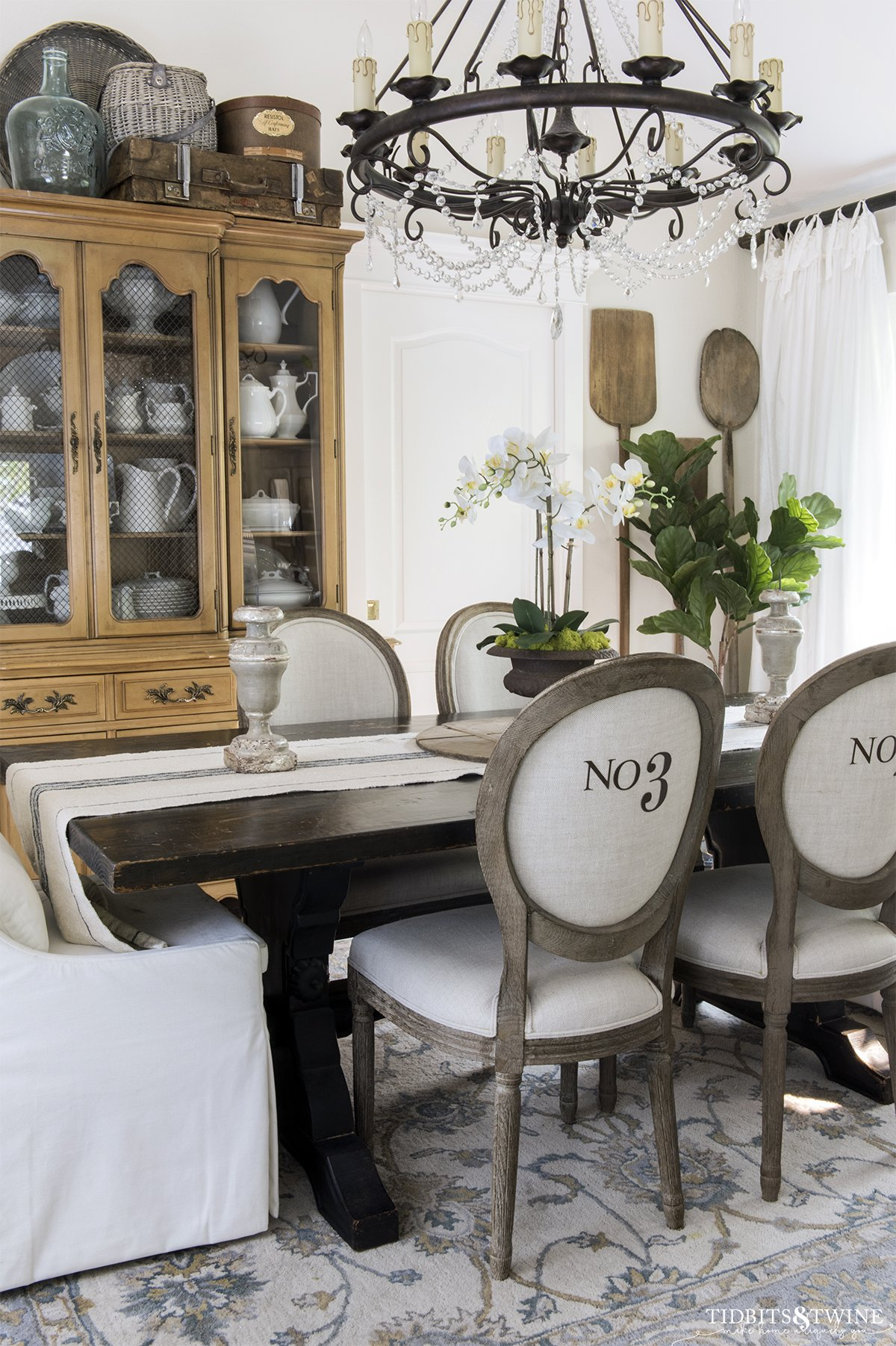 round french linen chairs with numbers on the back in dining room with white orchid on the table and vintage bread paddles hanging on the wall