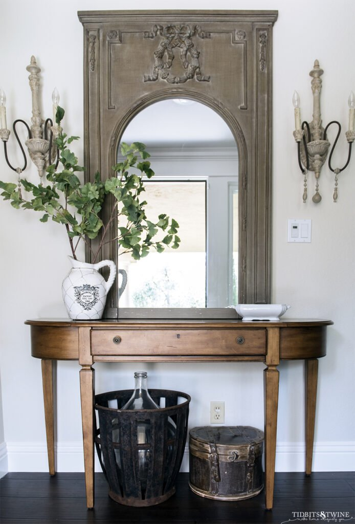 wood demilune console table with green trumeau french style mirror above and french sconces on either side on ballet white painted wall