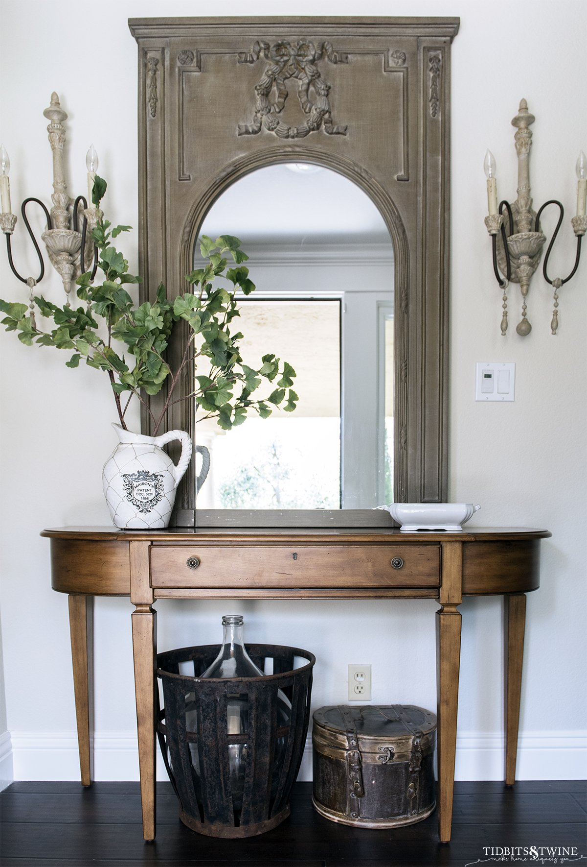wood demilune console table with green trumeau mirror above and french sconces on either side on ballet white painted wall