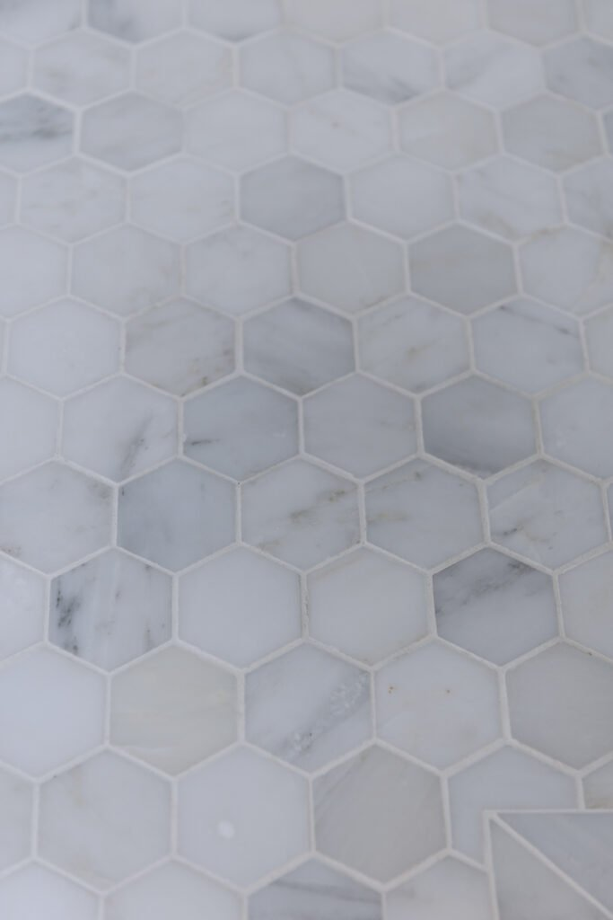 closeup of 2 inch white marble tile floor with white grout showing marble etching