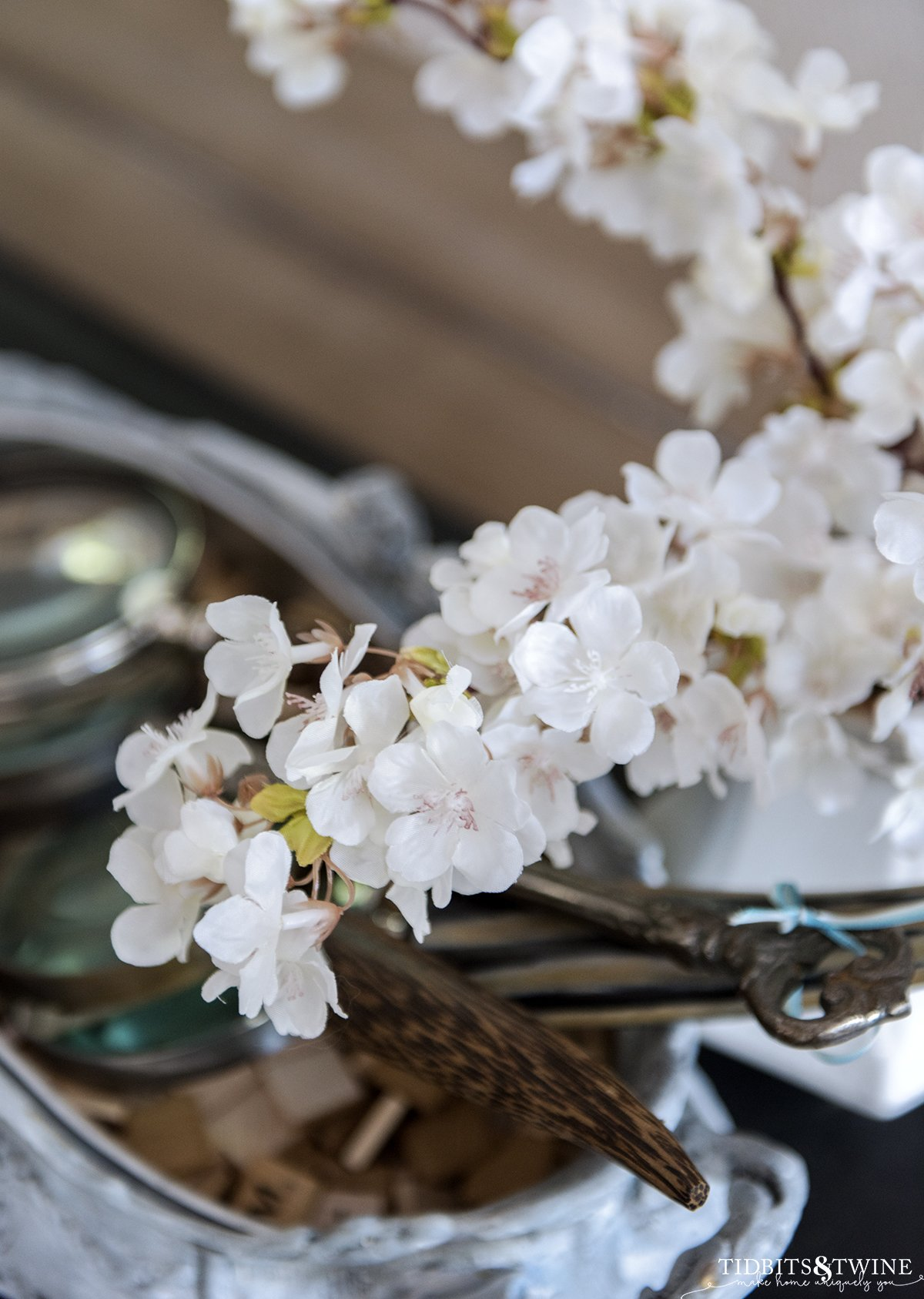 closeup of fake cherry blossom stems that are white with slight pink centers and magnifying glasses in the background