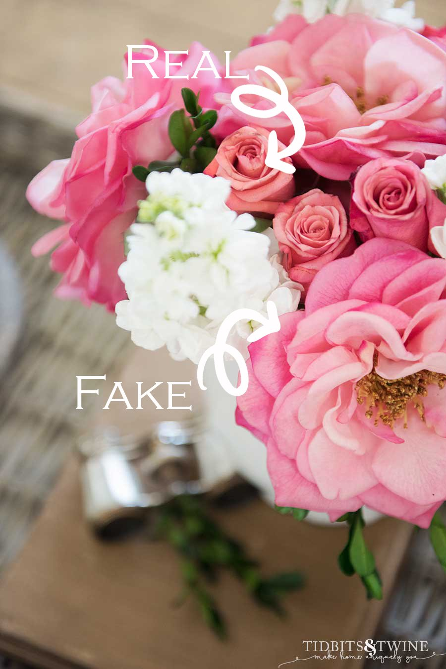 bouquet of pink rose buds and pink fake flowers with white stock and boxwood with opera glasses in the background