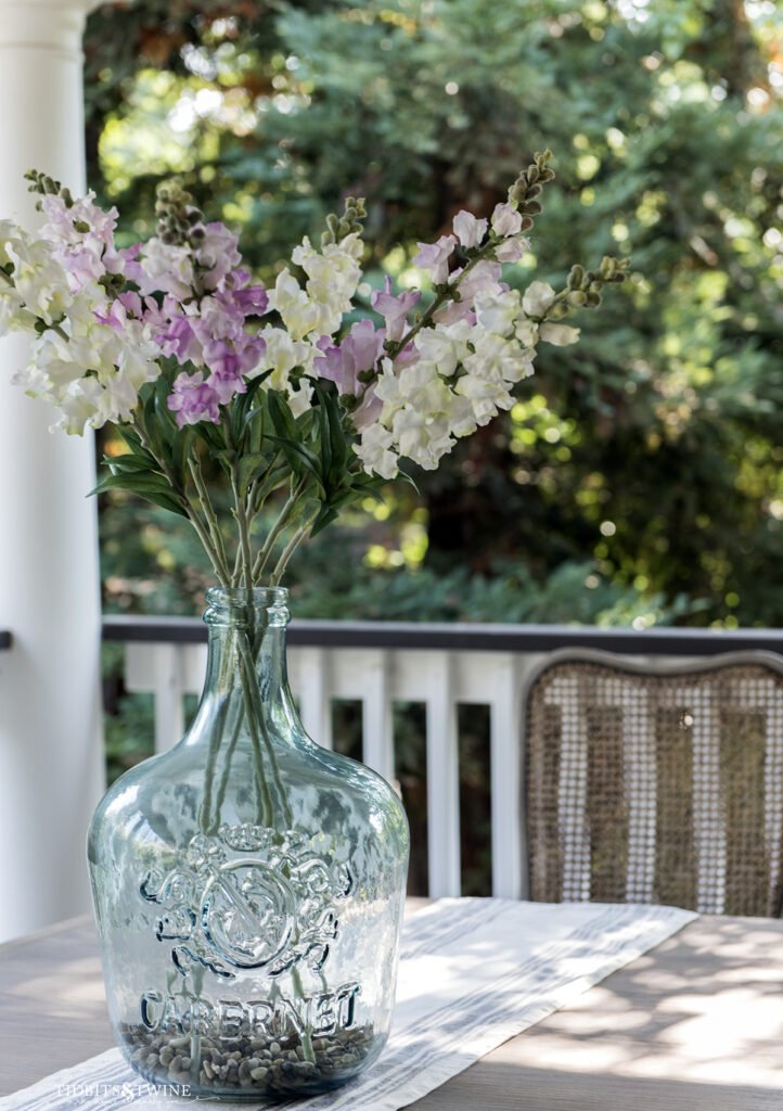 blue glass demijohn filled with white and purple fake snapdragons on a table outside on a porch
