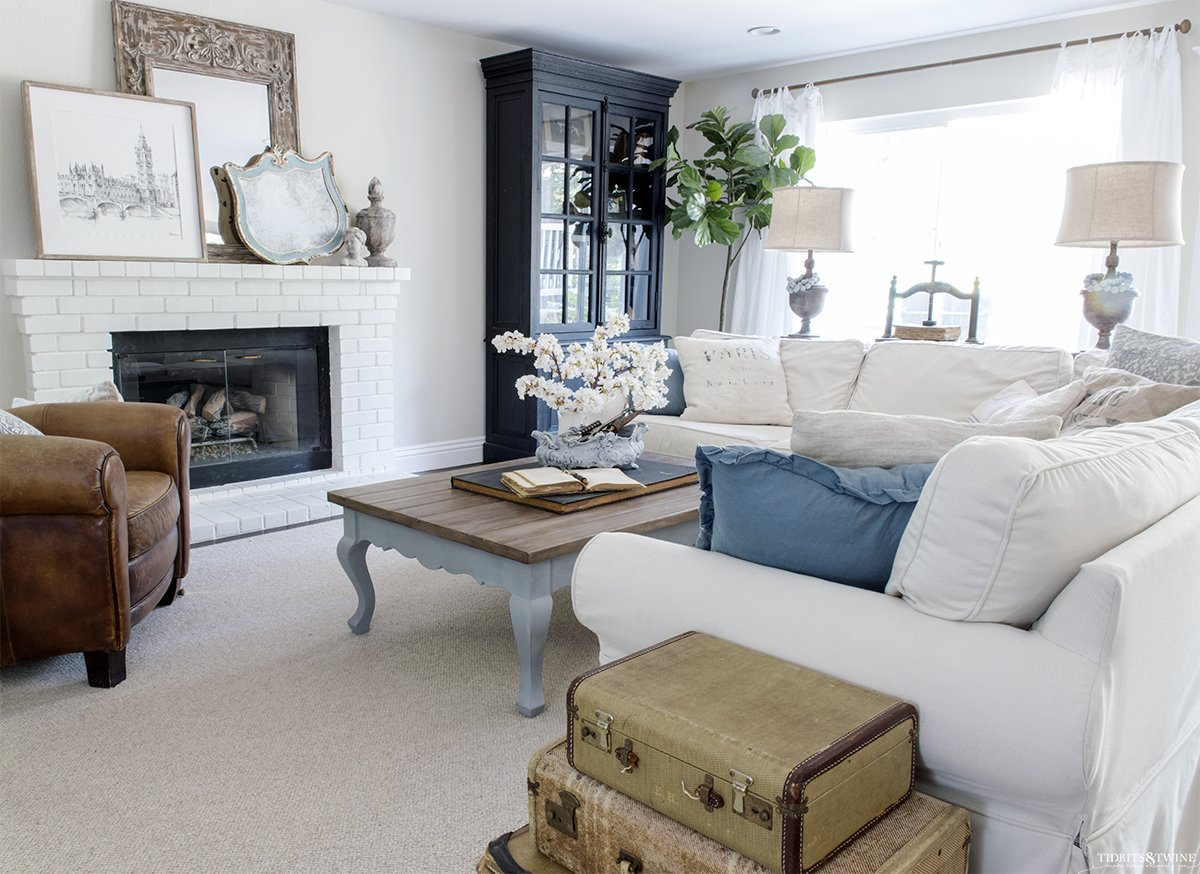 white slipcovered sectional with blue pillows and french blue coffee table white brick fireplace and black french cabinet