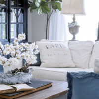 living room with white slipcovered sectional and blue throw pillows french coffee table with cherry blossoms in a vase on top