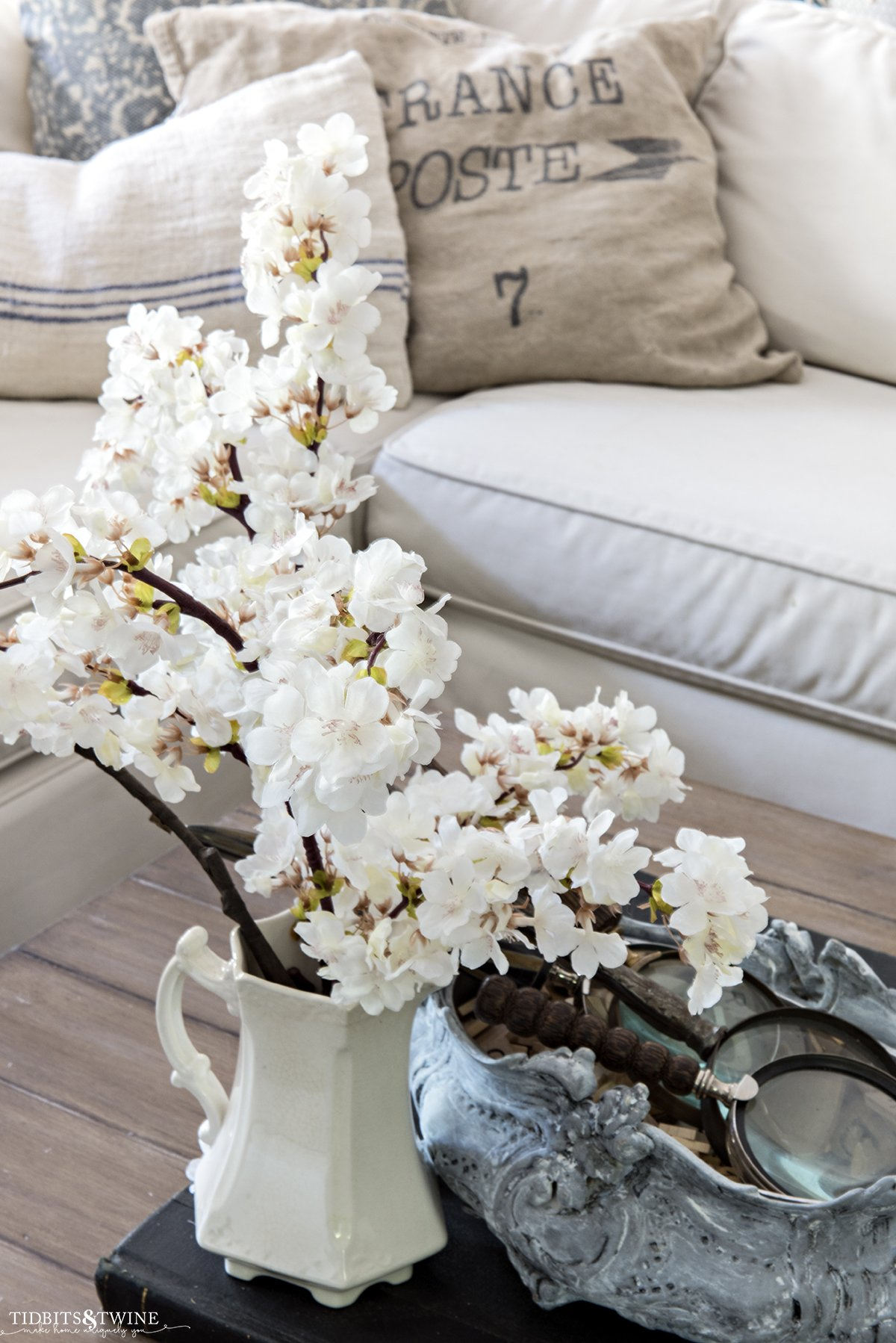 cherry blossom stems in an ironstone pitcher on coffee table with sectional sofa in background with french pillows
