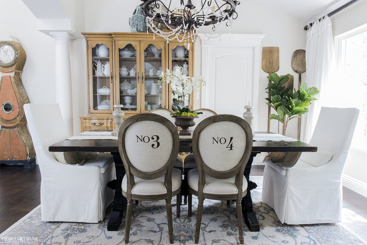 french style dining room with round number chairs white velvet head chairs vintage bread paddles on wall and antique mora clock