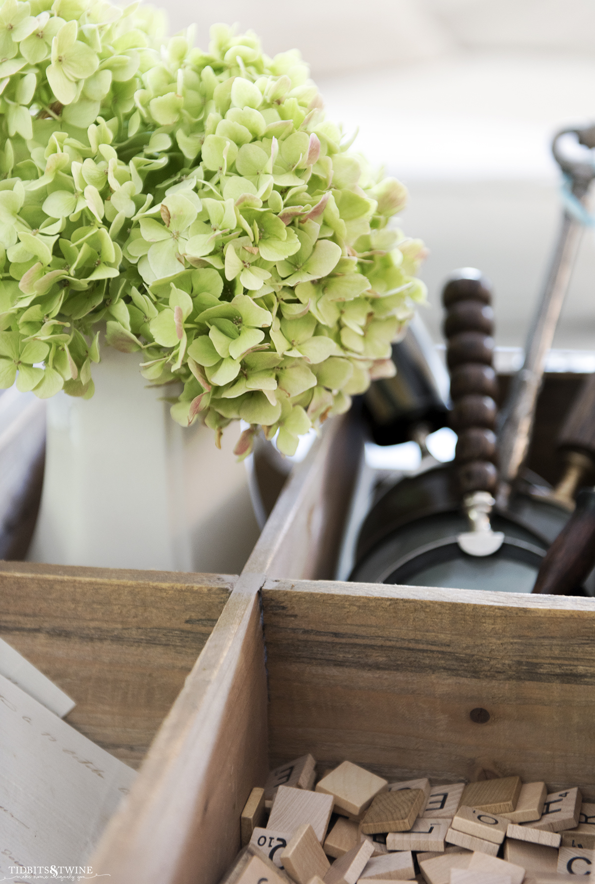 white ironstone vase filled with green hydrangea that are drying in a wooden box with magnifying glasses and scrabble tiles on coffee table