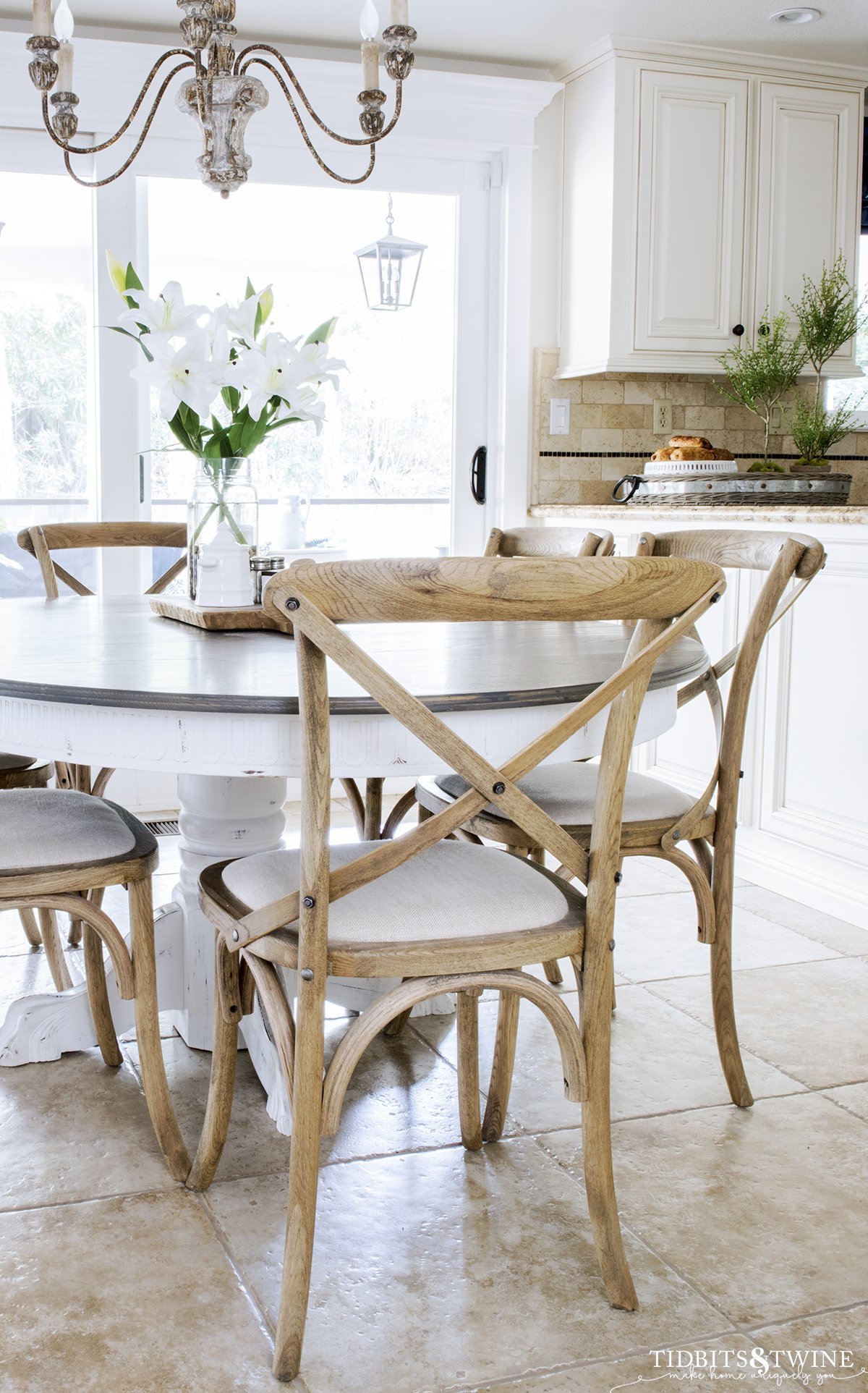 farmhouse kitchen with travertine tile floor and crossback chairs and french country chandelier with white lillies on the table