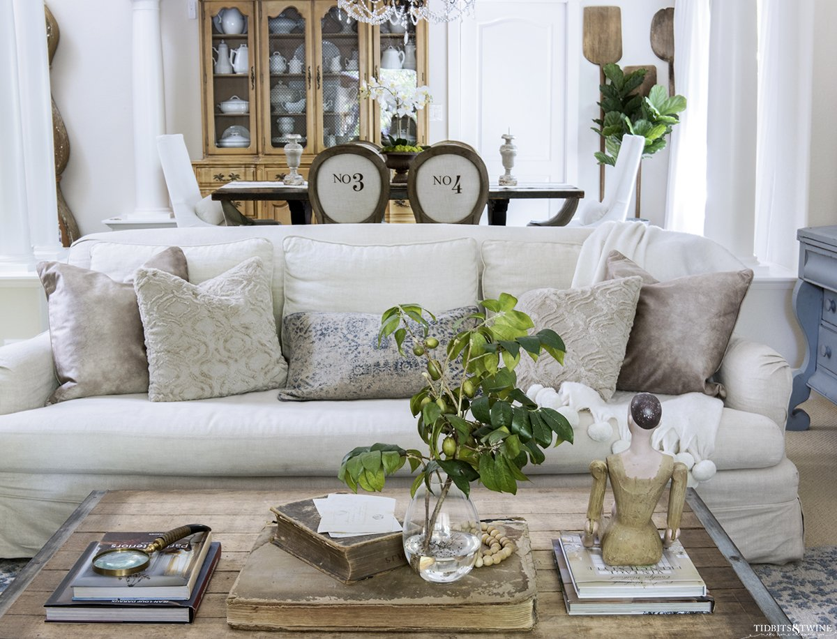 linen slipcovered sofa with beige decorative pillows and industrial coffee table in front and dining room in background with french round numbered chairs