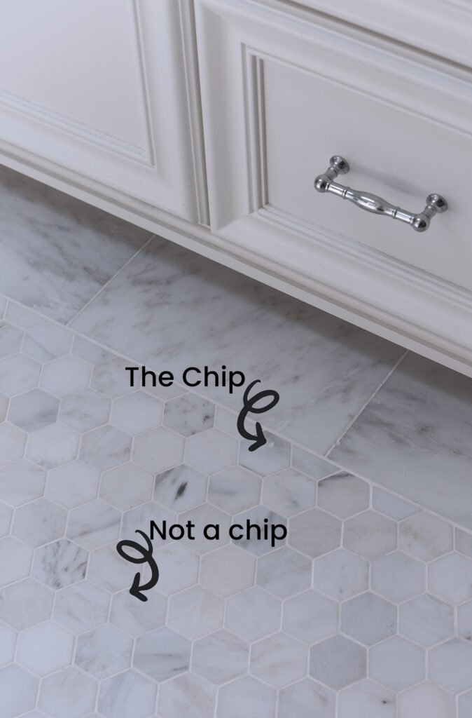 bathroom floor with two inch hex marble tile next to custom white bathroom vanity showing chip in tile