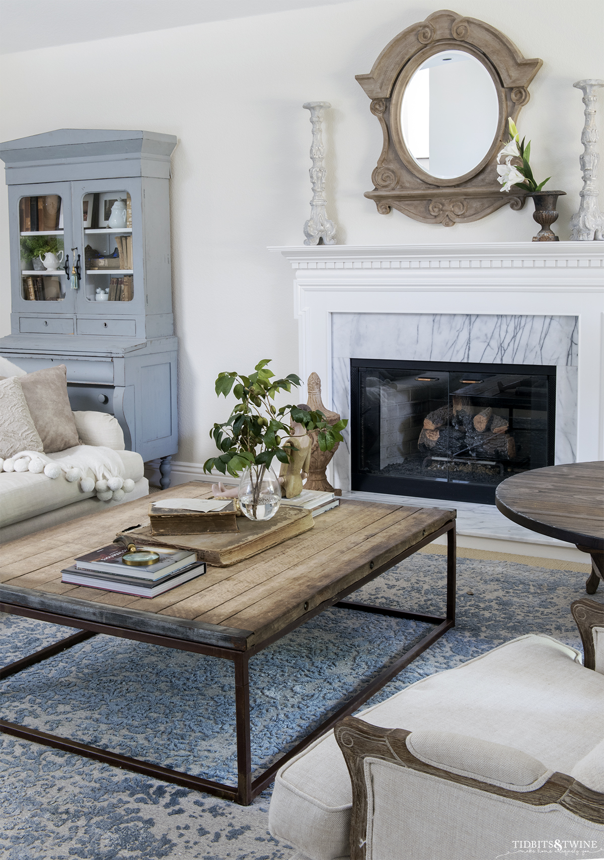 Industrial coffee table in front of white traditional fireplace with french blue cabinet next to it