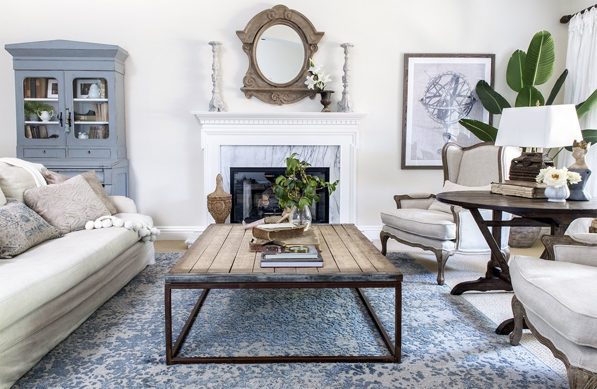 living room with slipcovered linen sofa and french wingback chairs and industrial coffee table on blue rug