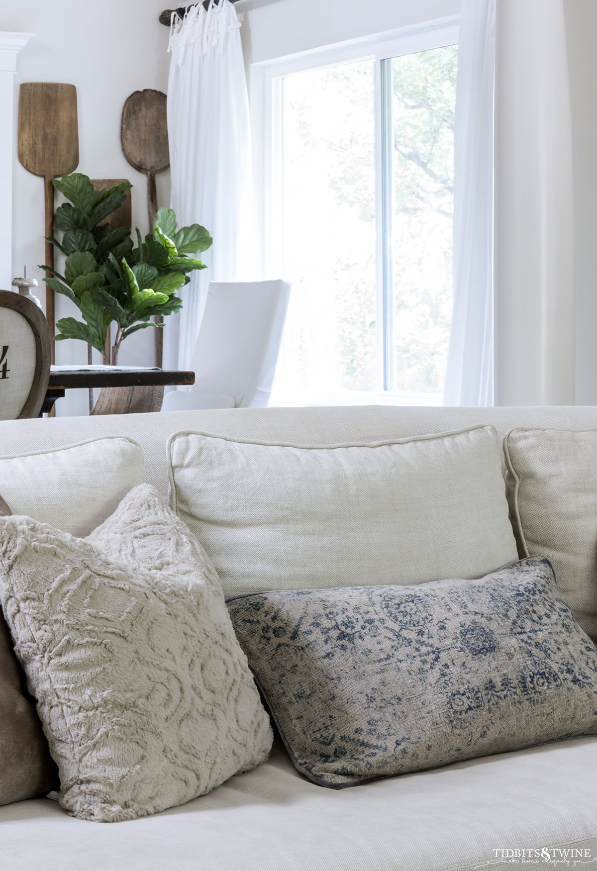 beige linen slipcovered sofa with throw pillows in beige faux fur and vintage lumbar pillow