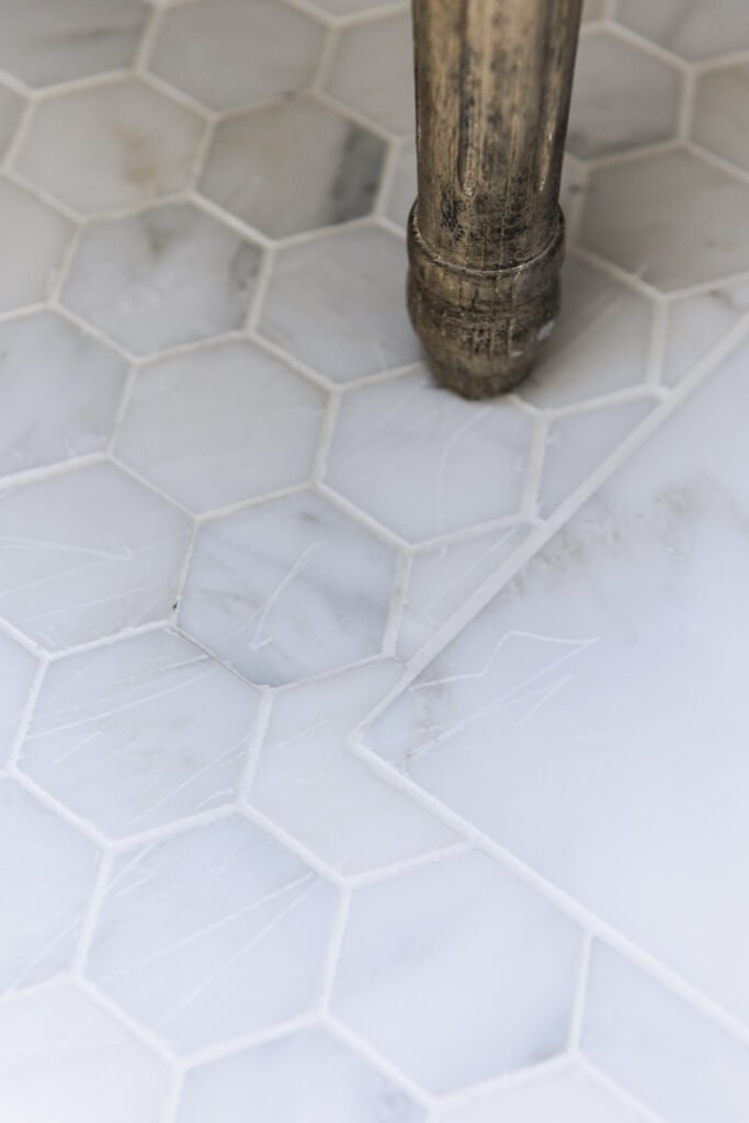 closeup of two inch hex marble tile floor in bathroom showing scratches from a chair leg