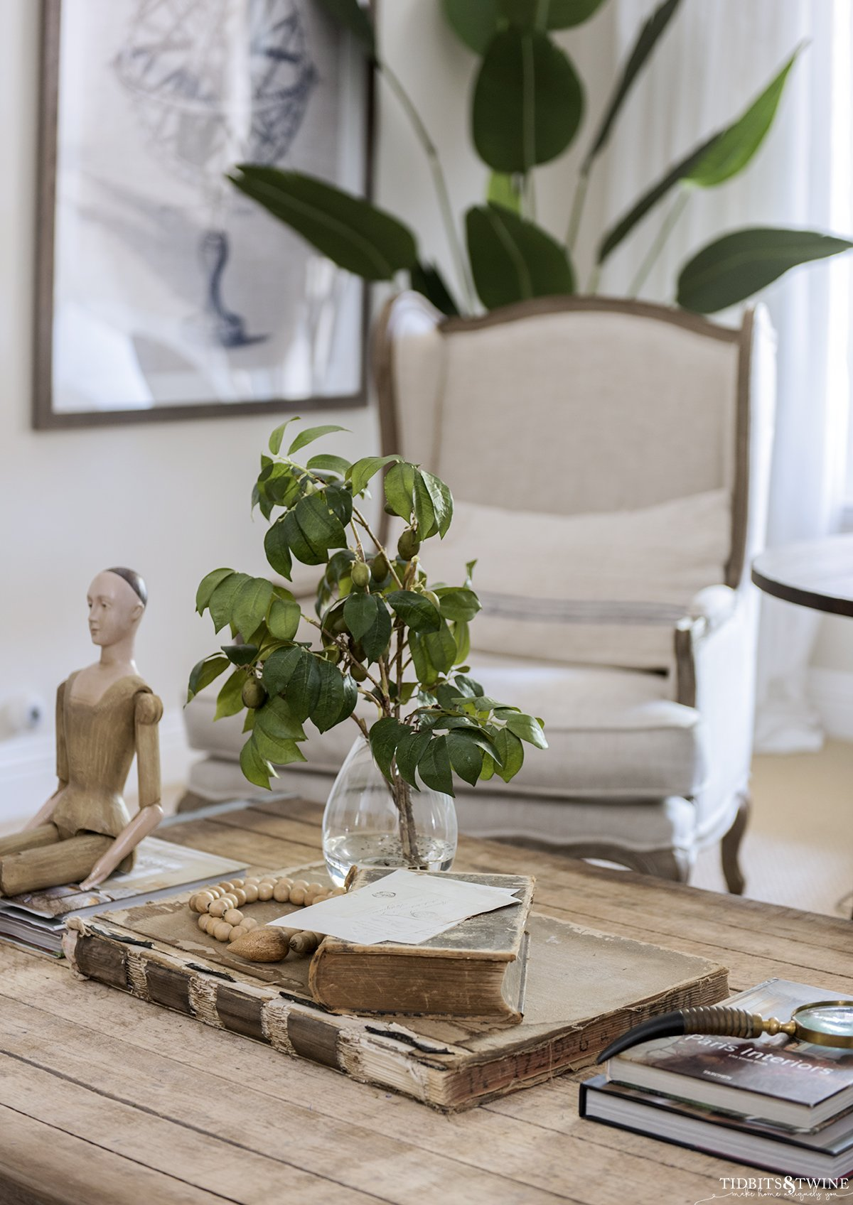 neutral living room with wooden top coffee table with old books on top and a vase with olive branches next to santos doll with french wingback chair in background