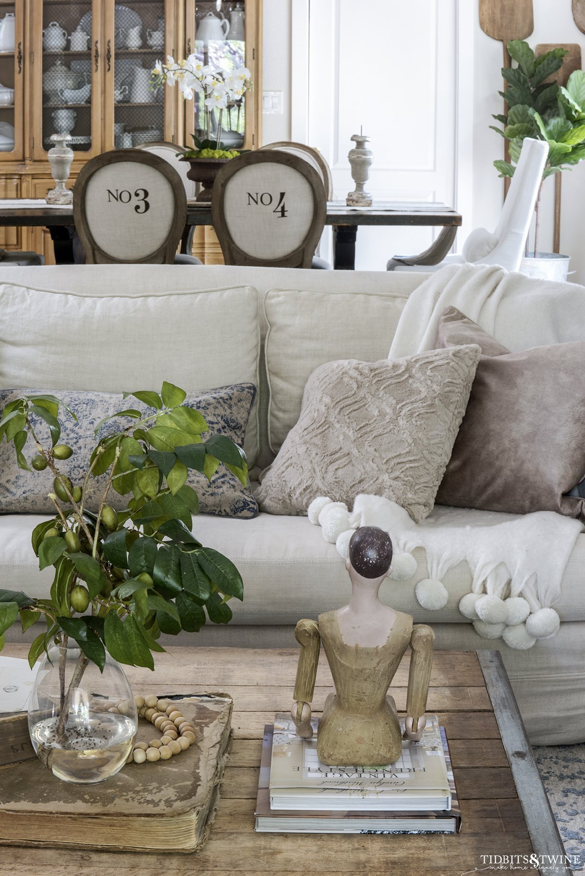 industrial coffee table with santos doll in front of linen sofa with dining room in background with numbered chairs