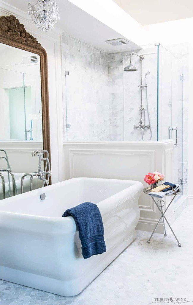 white marble bathroom with freestanding tub next to pony wall and large wood french mirror behind the tub