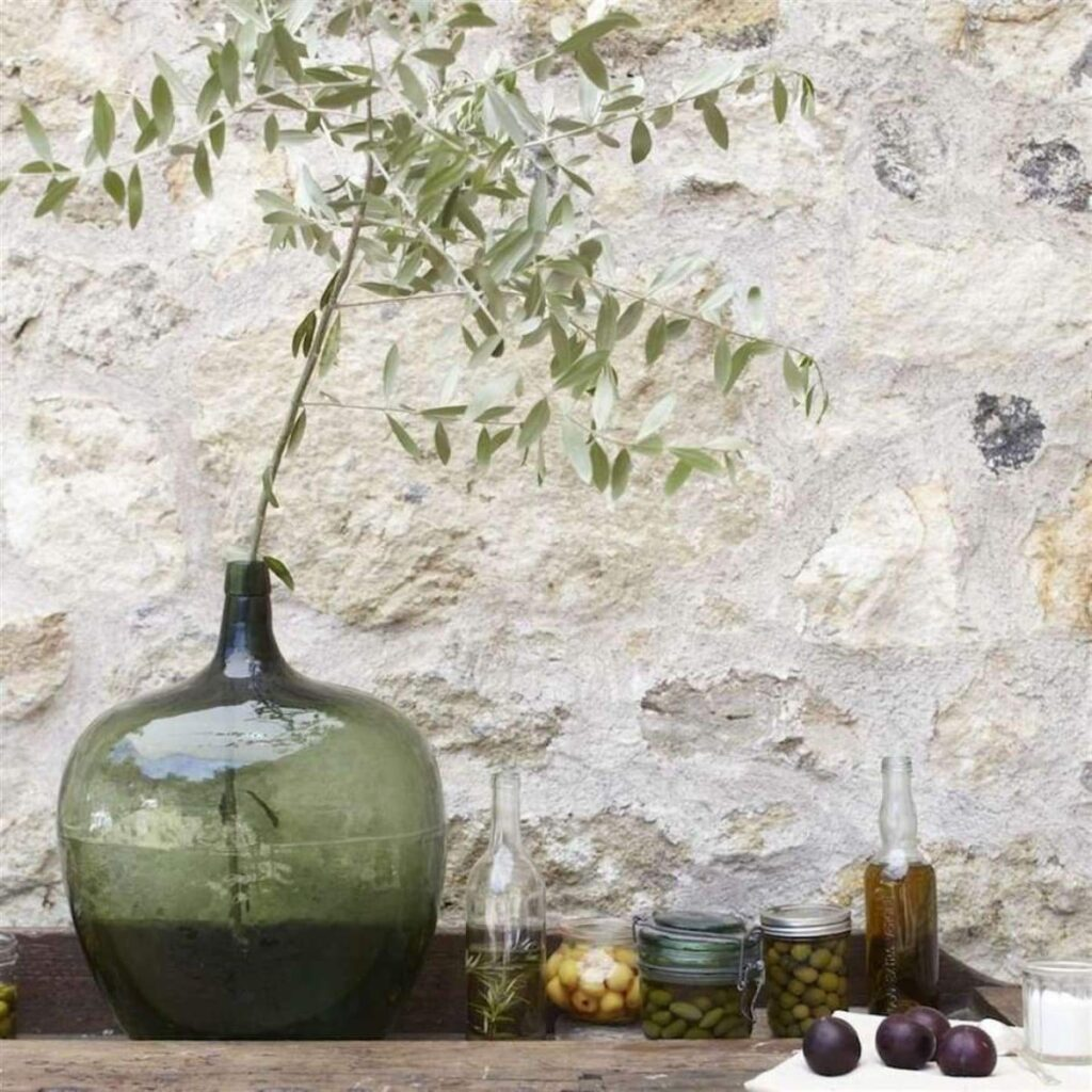 antique green demijohn holding a single olive branch next to jars full of olives and olive oil against a rock wall
