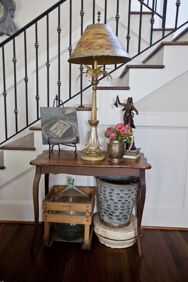 small table against a stair wall holding a lamp and a silver pitcher with flowers and underneath an antique olive bucket and crated demijohn