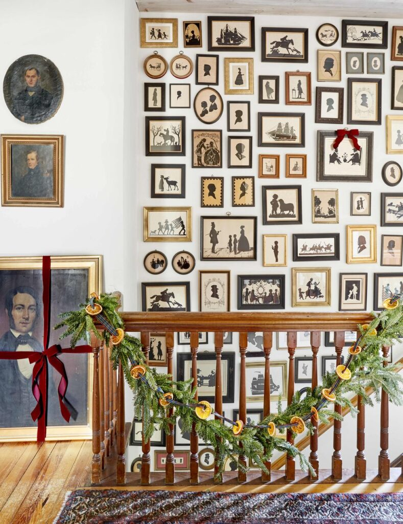 staircase wall filled with silhouette artwork in gold and black frames with christmas  garland on the banister