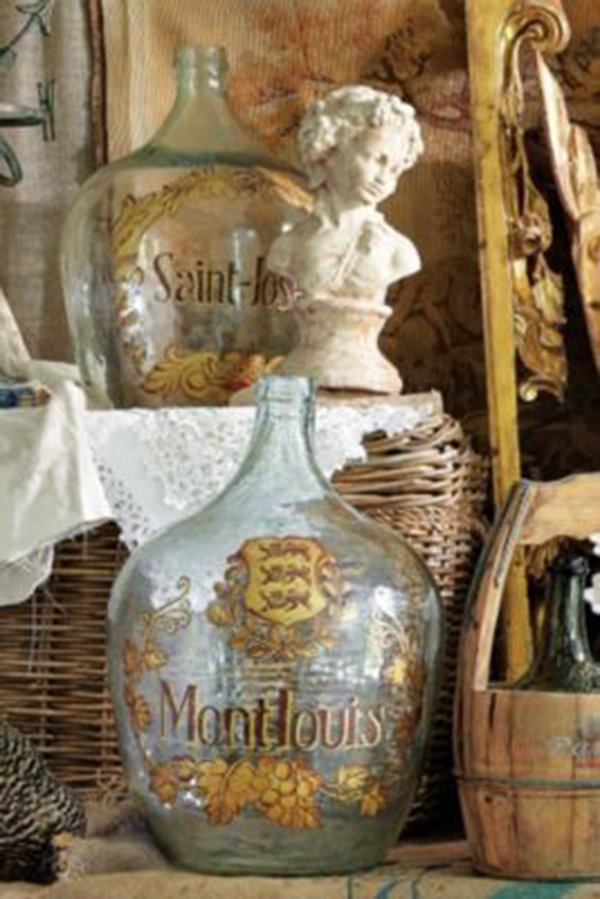 closeup of antique wine demijohn with gold paint on a clear bottle and basket and bust in the background