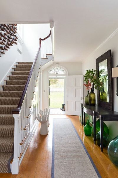 entryway with long hall table with green demijohns underneath and wood floor and stairs with white railing