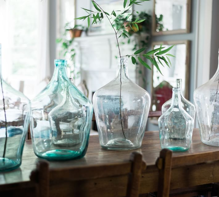 collection of blue and clear demijohns on a table one holding a single green stem