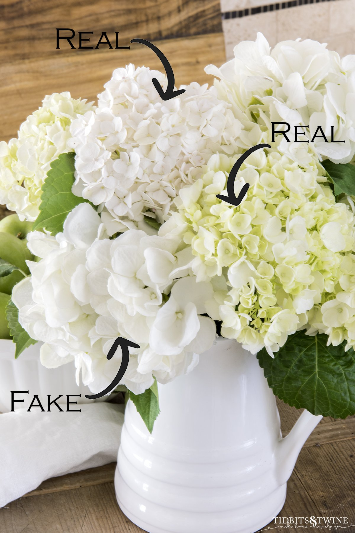 Closeup of white hydrangeas in a white pitcher with text overlay showing which are real and which are fake