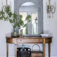 trumeau mirror above entry table flanked by french sconces with demijohn and basket underneath the table