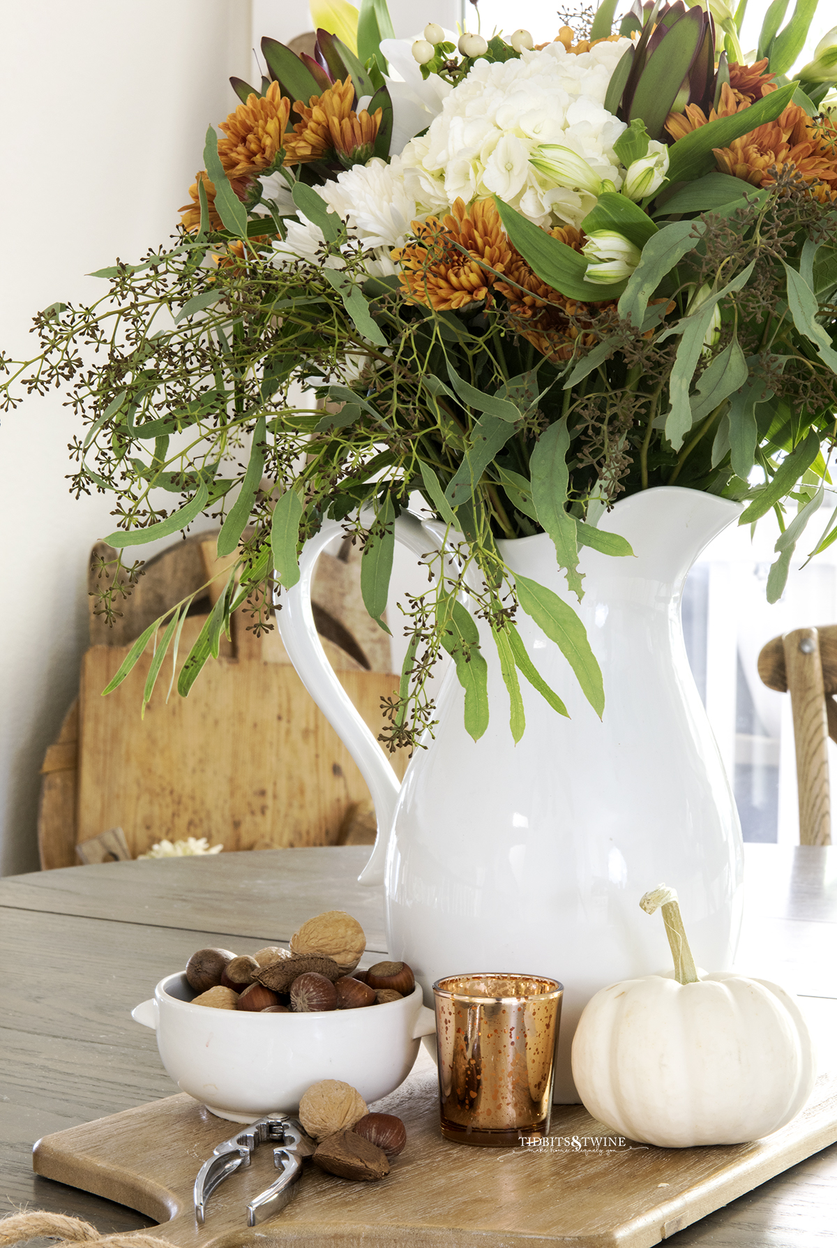 fall flower arrangement with white hydrangea and rust chrysanthemum in white pitcher on kitchen table with bowl of nuts