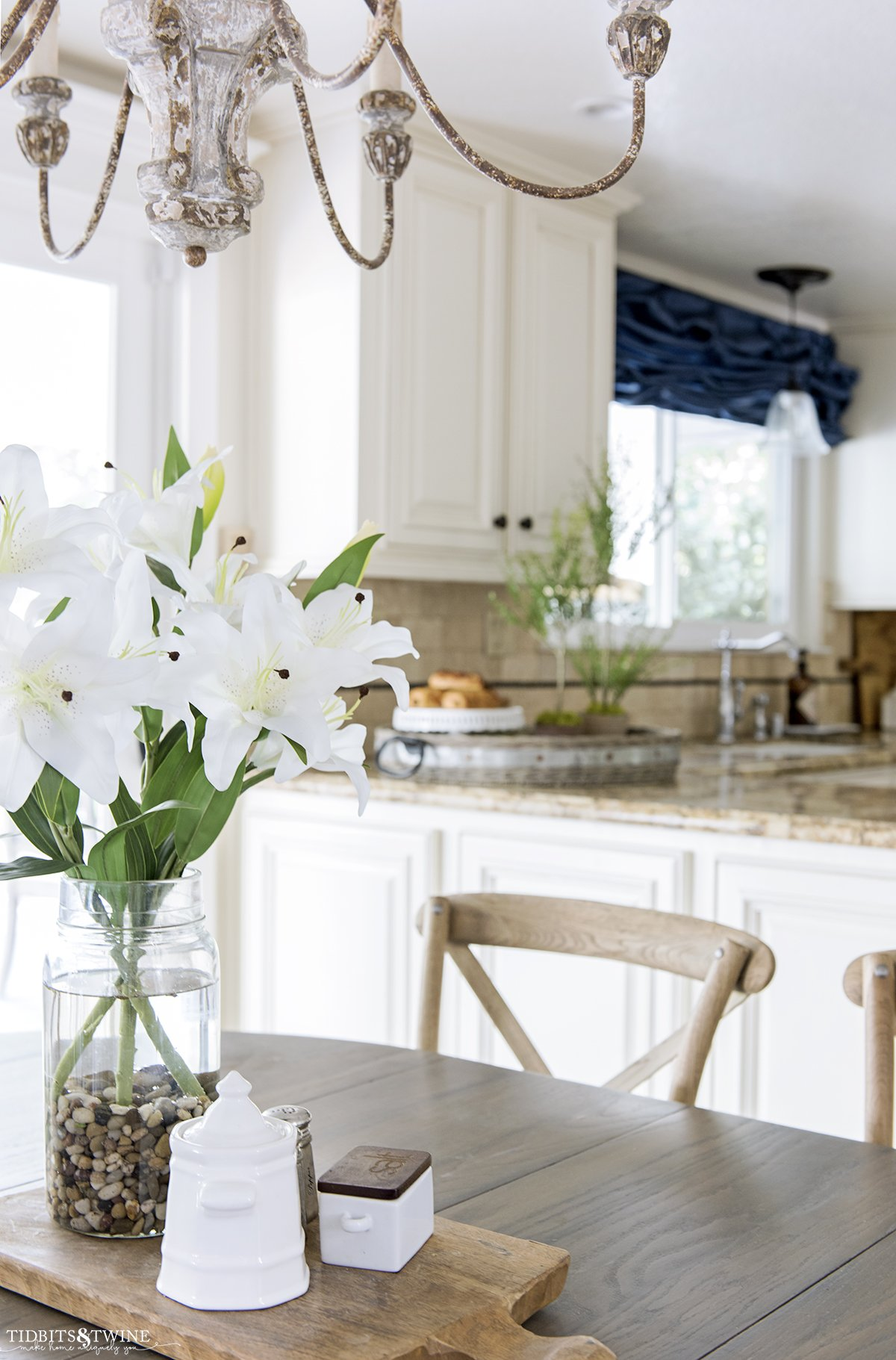farmhouse kitchen with white lillies in center of table crossback chairs and myrtle topiaries in background