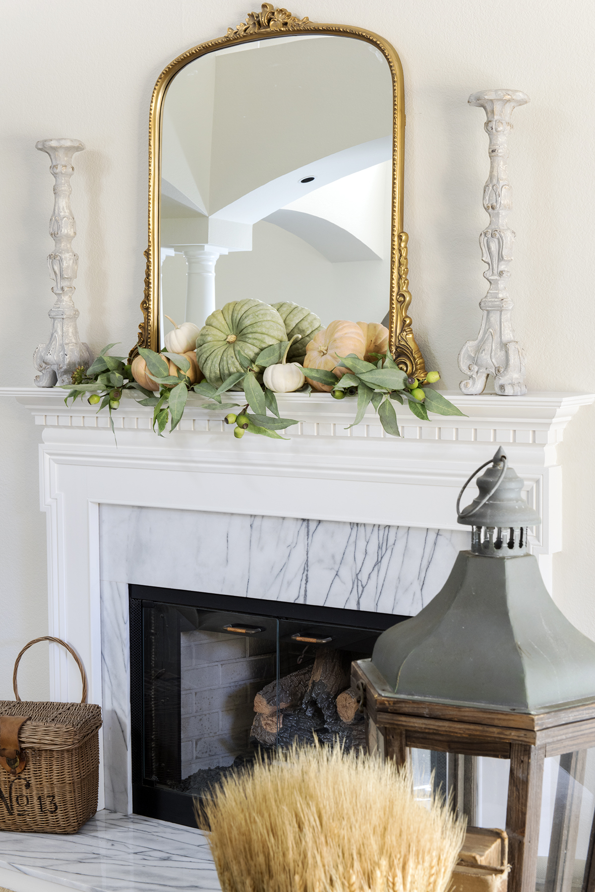 white fireplace with cararra marble decorated for fall with gold mirror and pumpkins and basket on hearth