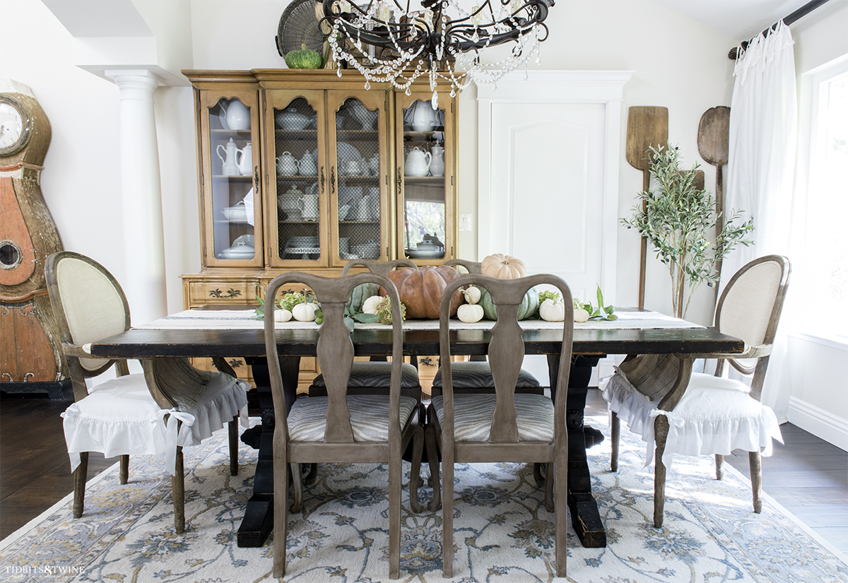 french dining room decorated for fall with pumpkins down center of table chairs with ruffle seat covers and hutch with white ironstone
