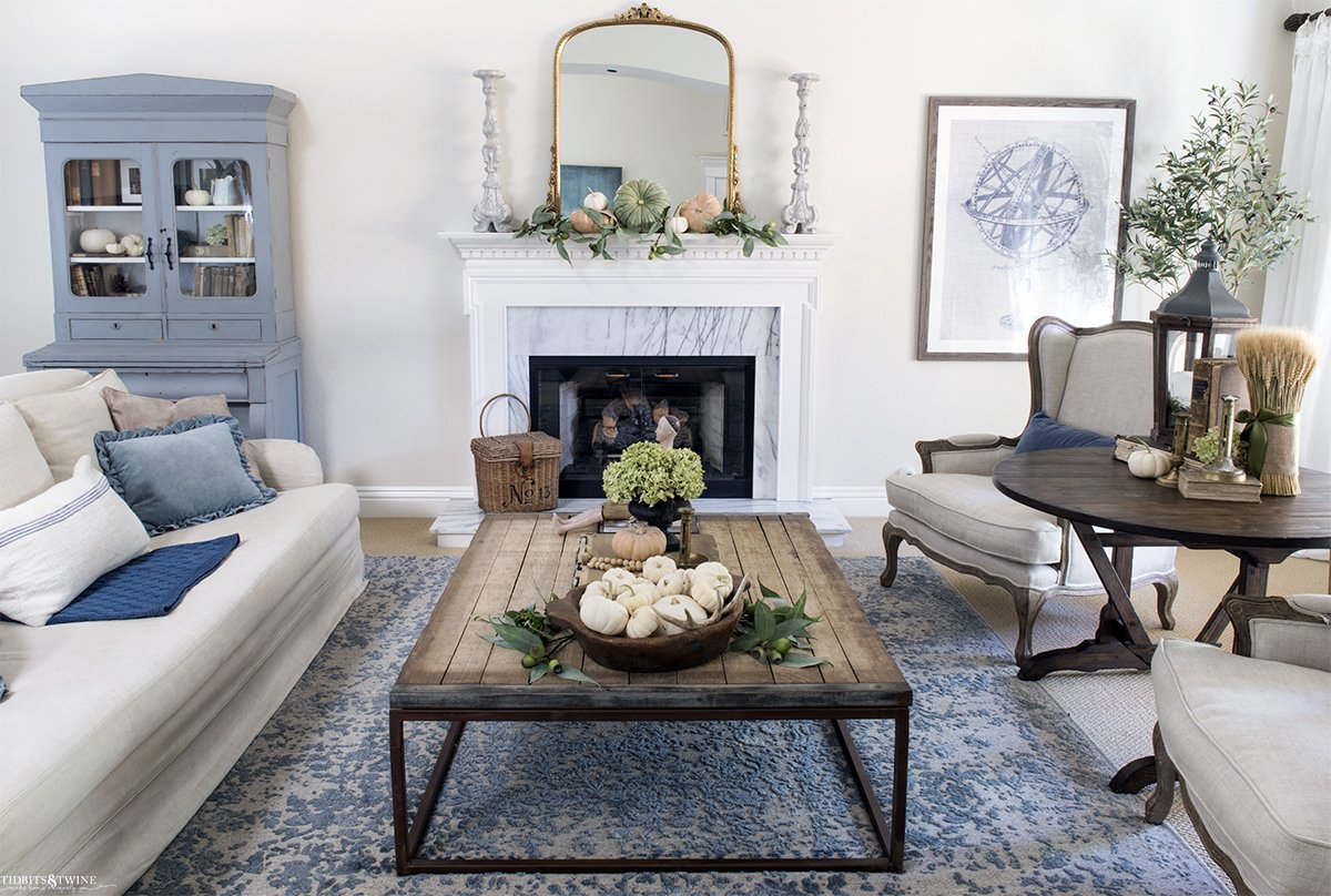 blue and white french living room with fireplace linen furniture and industrial coffee table decorated for fall with white pumpkins