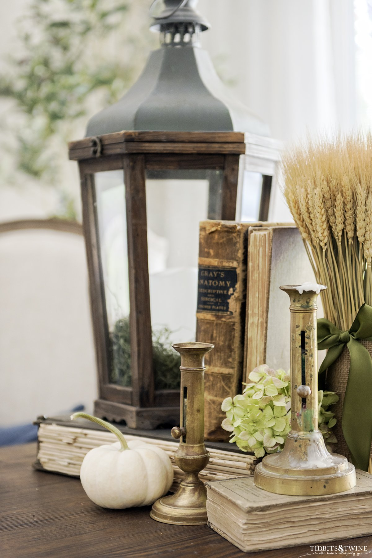 side table styled with wooden lantern old books brass candlesticks and wheat for fall