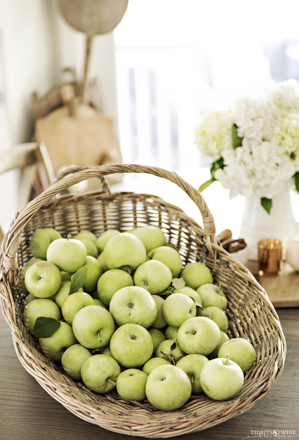 harvest basket full of green apples on kitchen table with white hydrangeas in a pitcher in the background with a collection of breadboards in the corner