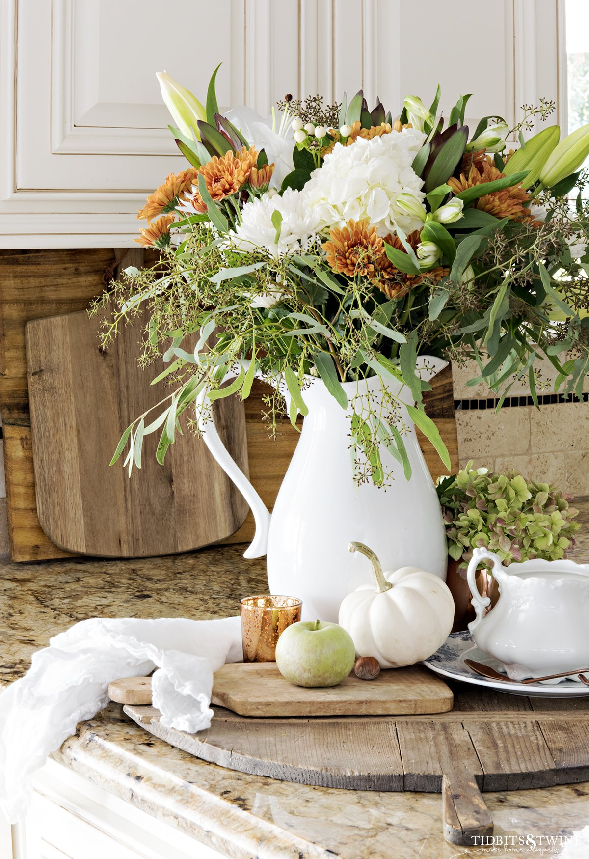 kitchen counter with fall vignette of white green and copper flowers in white pitcher on antique bread board with white pumpkins and apples