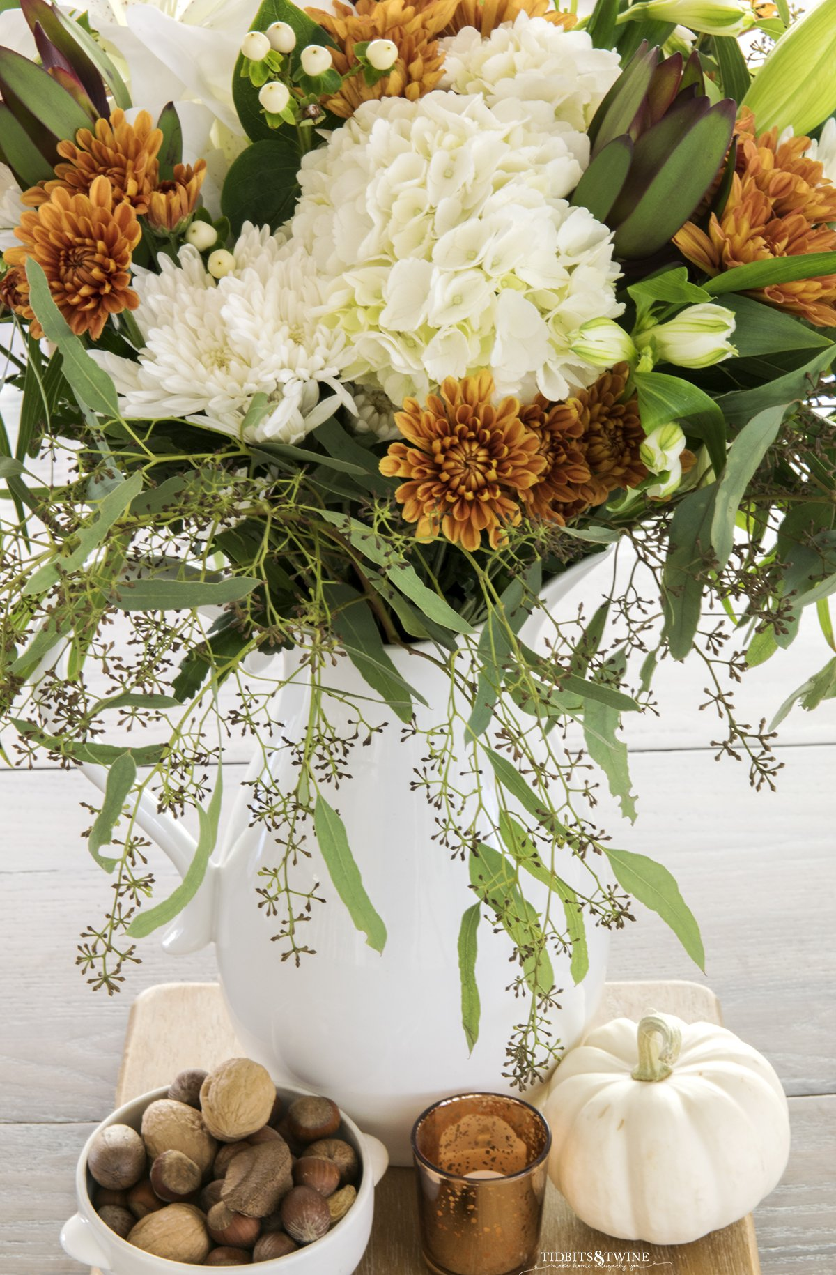 top down view of flower arrangement with white hydrangea and rust chrysanthemum in white pitcher