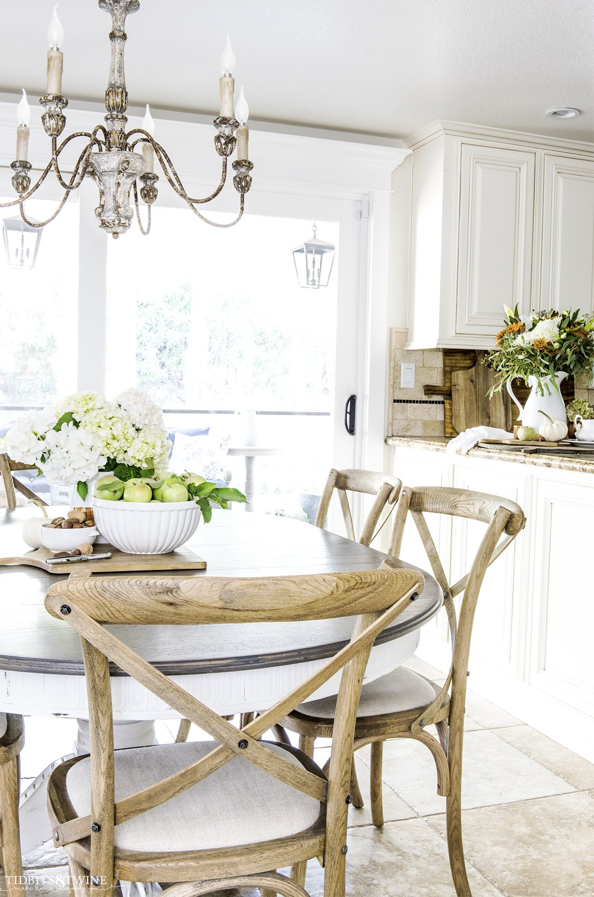 kitchen with white cabinets and granite counter with farmhouse table decorated for fall with apples hydrangea and copper accents