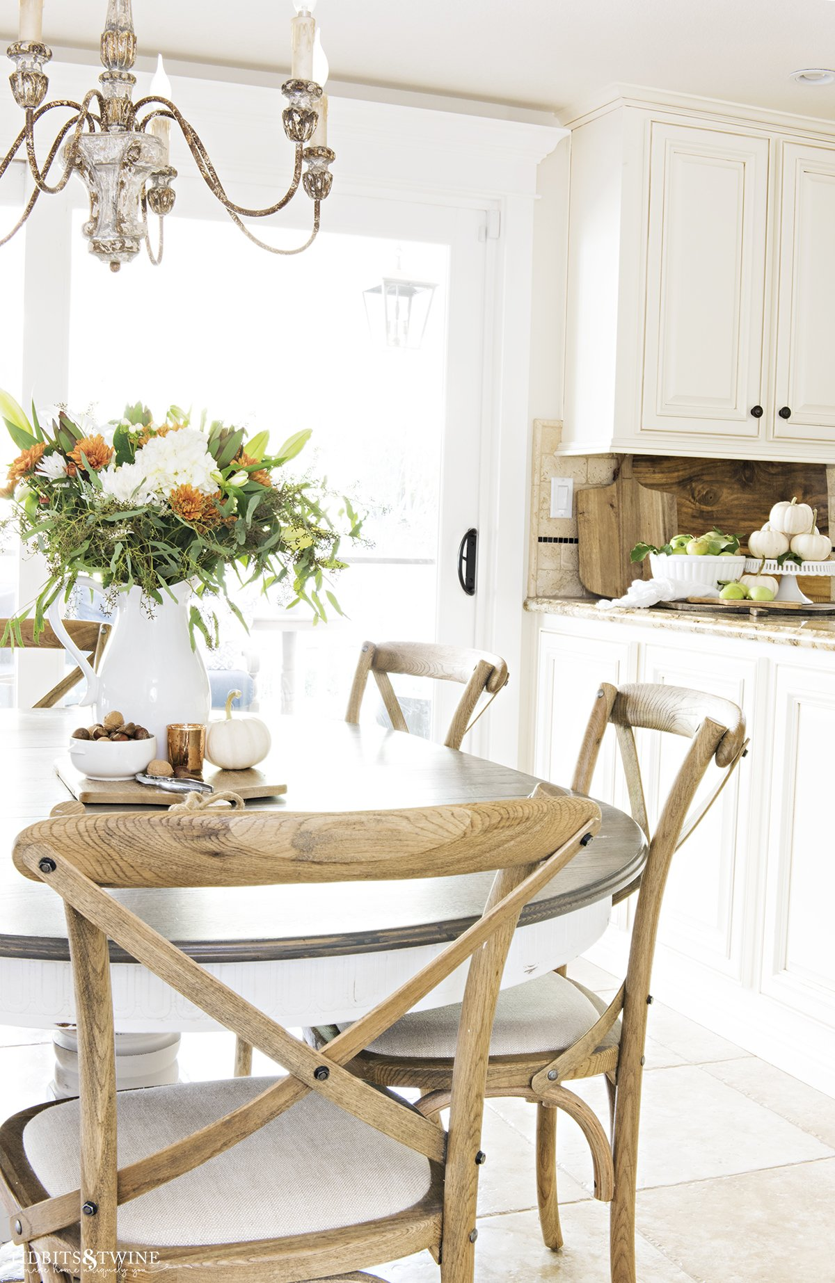 french country fall kitchen decor with table with white pitcher of fall flowers and crossback chairs and bowl of apples and pumpkins on countertop