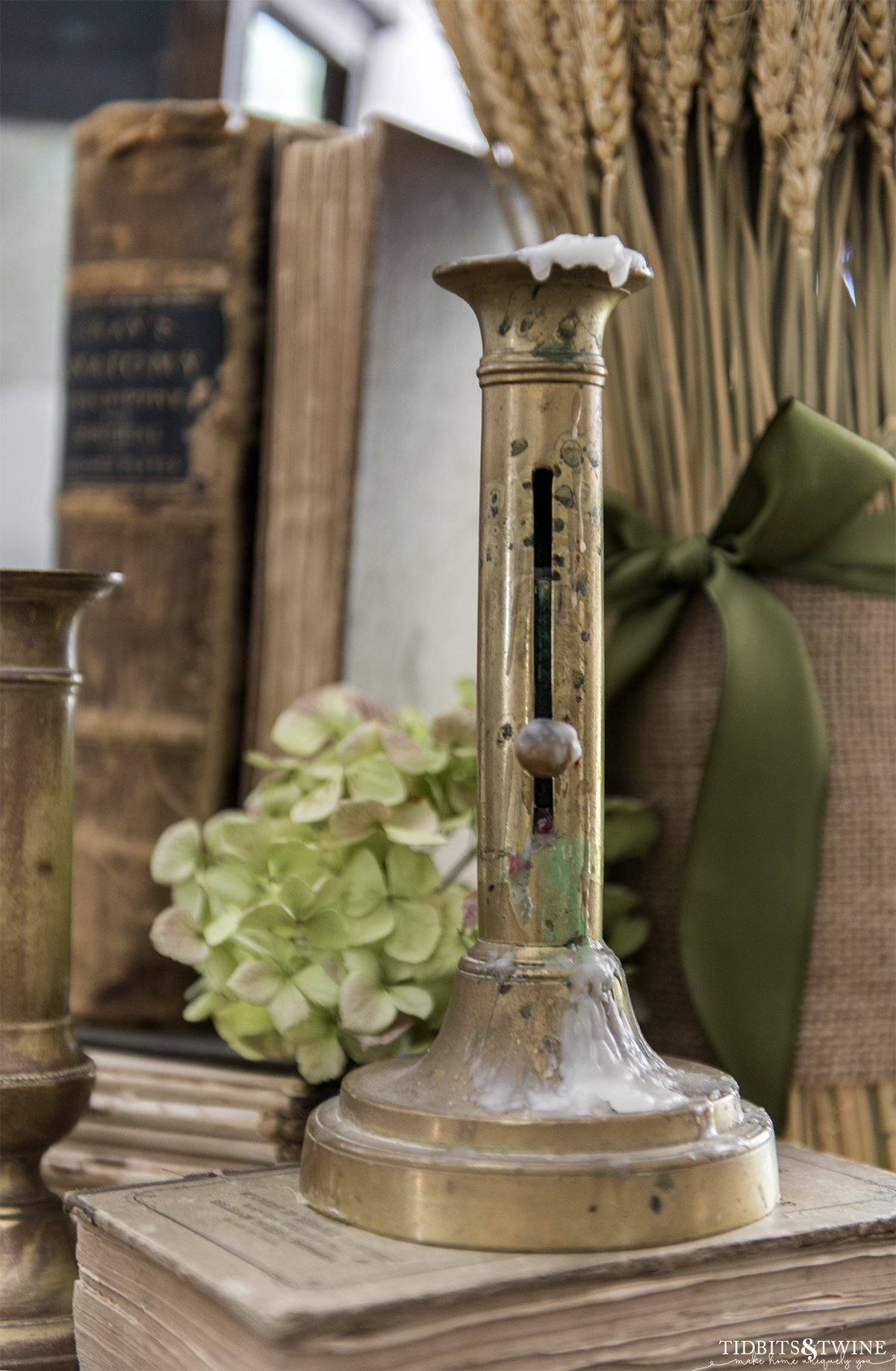 antique french brass candlestick sitting on old books with dried hydrangea and wheat bouquet in background