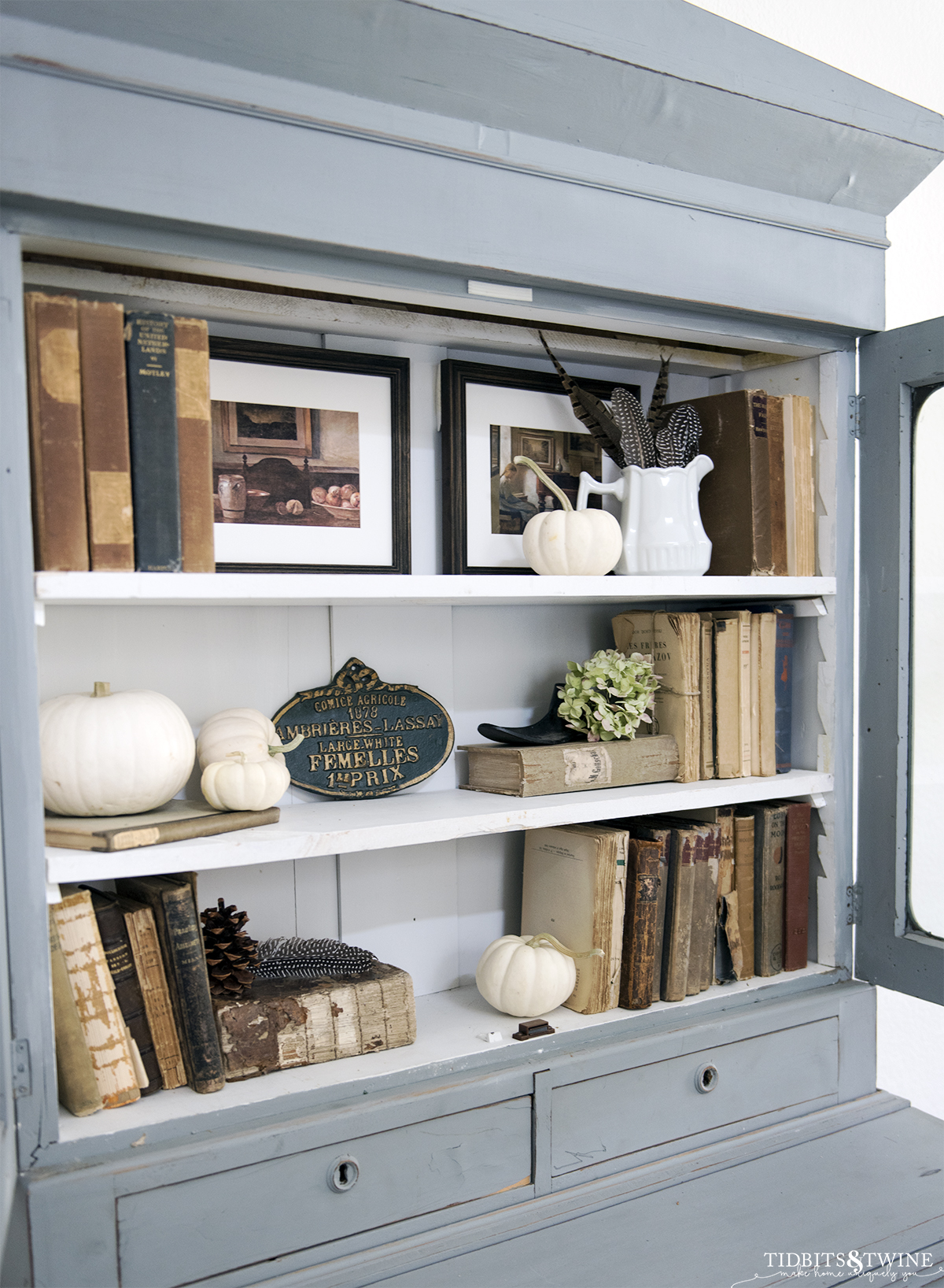 antique blue cabinet with three white shelves styled with old books art pumpkins and hydrangea for fall